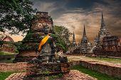 Buddha at Wat Phra Sri Sanphet temple ruins under sunset sky. Ayutthaya Thailand