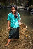 Cute Asian girls with baskets near tropical waterfall. Laos