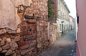 Narrow road between old damaged stone houses