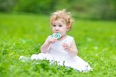 Beautiful baby girl with curly hair wearing a white dress eating candy in a park