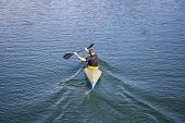 stock photo of canoe boat man  - Man in a canoe rowing on the tranquil lake - JPG