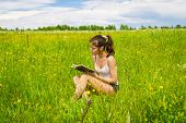 Young Woman Reading Book On Meadow
