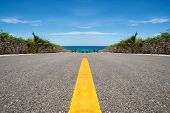 Road with yellow line ending in tropical sea ocean