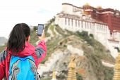 woman hiker taking photo with cell phone at potala palace,tibet ,china