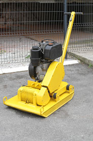 foto of vibration plate  - Yellow vibratory plate compactor at construction site - JPG