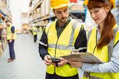 stock photo of team  - Warehouse team working together with clipboard in a large warehouse - JPG