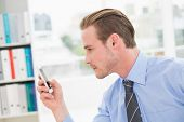 Focused businessman text messaging in his office
