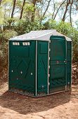 Green Plastic Toilet Booth In The Forest.