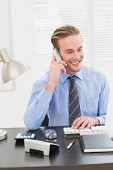 Smiling businessman working and phoning at his desk in his office