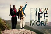 Excited couple reaching the top of their hike and cheering against enjoy life more