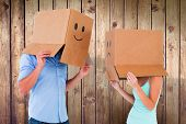 Couple wearing emoticon face boxes on their heads against wooden planks