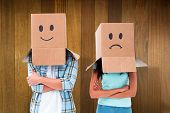 Young couple wearing sad face boxes over head against wooden surface with planks
