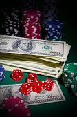 Dollars chips and dices on green table