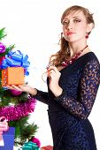 Portrait Of A Beautiful Young Woman Holding A Present Near The Christmas Tree