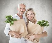 Happy couple carrying paper grocery bags against weathered surface