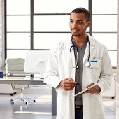 Young black male doctor holding tablet, looking away.