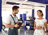 Happy female customer talking to car mechanic in auto repair shop, smiling happy.