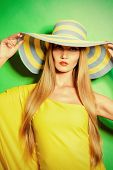 Portrait of a stunning fashionable lady in bright yellow dress posing over  green background. Beauty, fashion concept. Colors of summer.