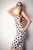 Fashionable lady in polka-dot dress posing near white brick wall. Beauty, fashion concept. Optics.