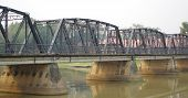 stock photo of flat-foot  - Multi span  Iron Arched Road Bridge, painted flat black, with footpath crossing the river mounted on large concrete footings the width of the bridge.
