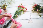 stock photo of carnation  - Female hands tying carnation bouquet with silk ribbon - JPG