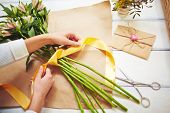 Female florist tying up fresh flowers with silk ribbon