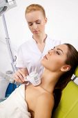 Young adult brunette pretty woman getting laser face treatment in medical spa center, skin rejuvenation concept