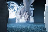 Happy senior couple holding hands against bright moon over arc de triomph