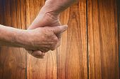 Elderly couple holding hands against wooden table