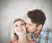 Handsome man kissing girlfriend on cheek against white background