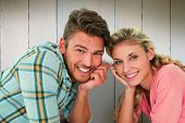 Attractive young couple lying and smiling at camera against wooden planks
