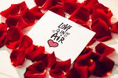 love is in the air against card surrounded by rose petals