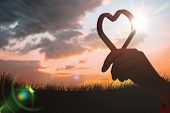 Red love heart against sun set