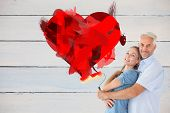 Happy couple hugging and holding paint roller against painted blue wooden planks
