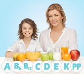 people, healthy lifestyle, family and food concept - happy mother and daughter eating healthy breakfast over blue background with vitamins