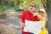 Happy tourist couple using map against rapids flowing along forest