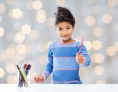 children, creativity and happy people concept - happy little girl drawing with coloring pencils over holidays lights background