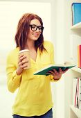 education concept - smiling redhead female student in eyeglasses with book and takeaway coffee in library