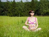 Pregnancy Woman Is Sitting On A Grass