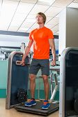 Gym squat machine exercise workout blond man at indoor
