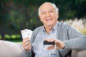 Portrait of happy senior man holding four aces while sitting on couch at nursing home porch