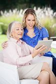 Smiling grandmother and granddaughter using tablet computer at nursing home porch