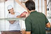Happy mature female butcher selling fresh meat to male customer at shop