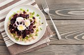 salad with beans, beetroot, egg, green onions on wooden background.