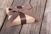 stock photo of gift wrapped  - Small gift wrapped in brown paper ribbon and bow on old wood boards - JPG