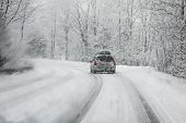 stock photo of slippery-roads  - Car driving during winter snow taken through a windshield covered with blured snowflakes - JPG