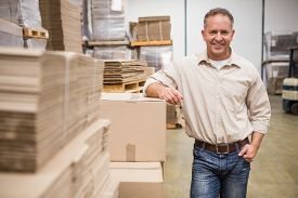 pic of warehouse  - Smiling warehouse worker leaning against boxes in a large warehouse - JPG