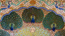 image of mumtaj  - Three ornate peacocks overlook an arched doorway in a courtyard of the City Palace - JPG