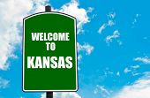foto of kansas  - Green road sign with greeting message Welcome to KANSAS isolated over clear blue sky background with available copy space - JPG
