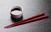 stock photo of soy sauce  - Japanese sushi chopsticks and soy sauce bowl on black stone background - JPG